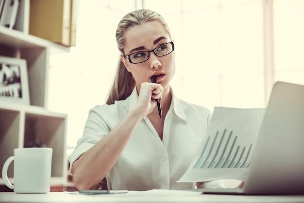 Geschäftsdame in den brillen studiert dokumente.
