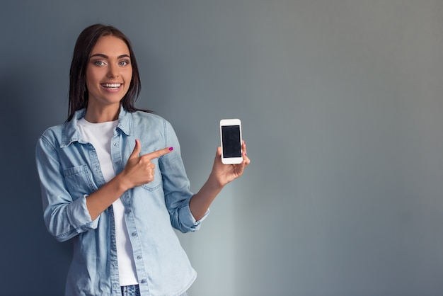 Geschäftsdame in der zufälligen kleidung hält einen smartphone. exemplar