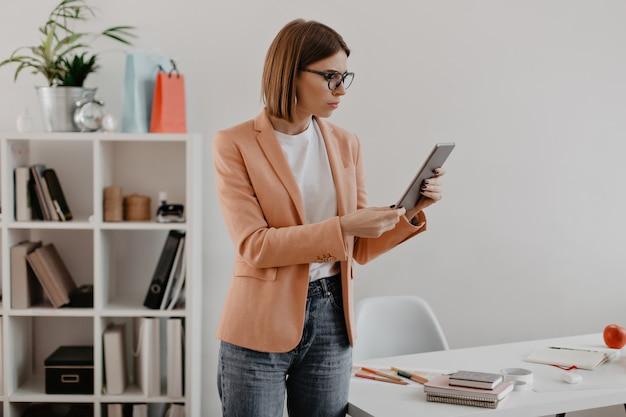 Geschäftsdame sieht auf tablette verwirrt aus. junge frau in der leichten kleidung, die über büro aufwirft.