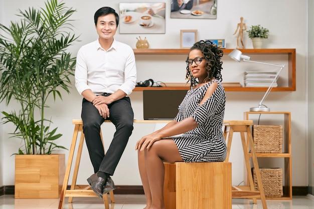 Geschäftsdame und geschäftsmann, die im modernen büro sitzen und kamera nach beendigung der arbeit betrachten