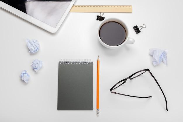Geschäftsdesktop mit notizbuch und kaffeetasse