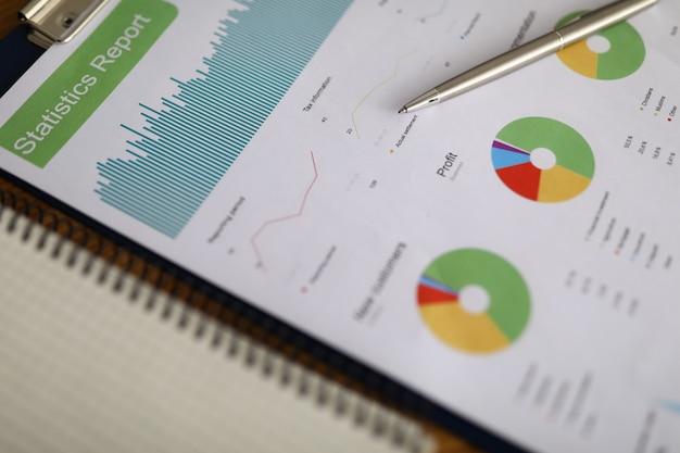 Geschäftsdiagramm mit silbernem stift liegen auf bürotischnahaufnahme