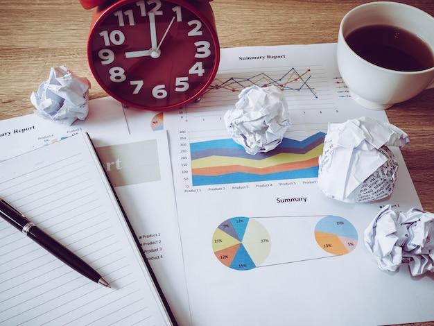 Geschäftsdiagramm mit zerknittertem papier und wecker auf holztisch.