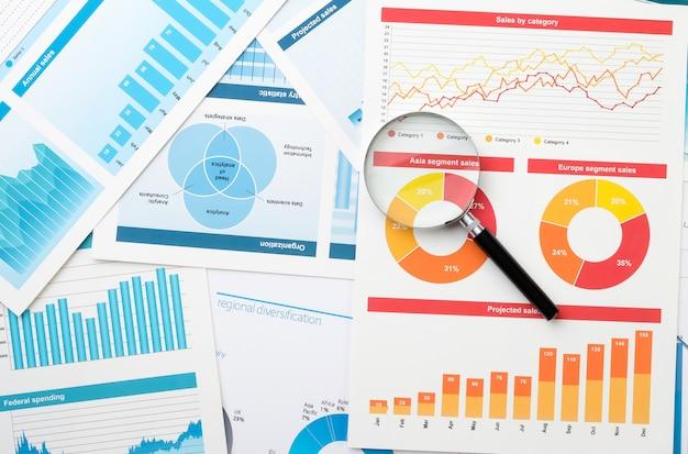 Geschäftsdiagramm und lupe auf dem desktop. das konzept der analyse und ermittlung von schlüsselinformationen in der wirtschaft.