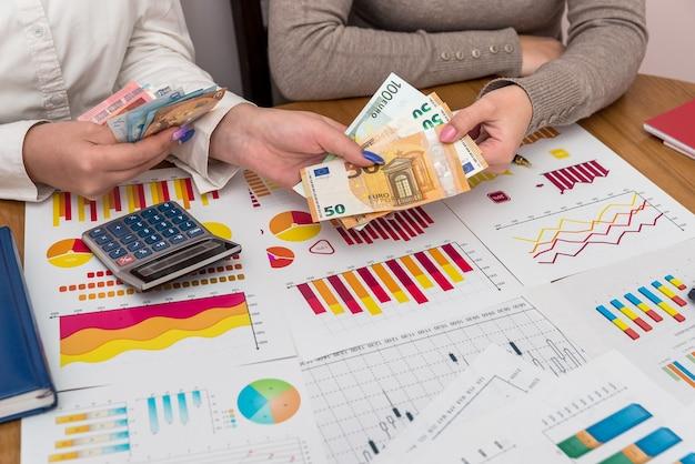 Geschäftsdiagramme mit weiblichen händen, die euro halten