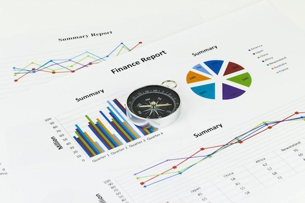 Geschäftsdiagramme und -finanzen mit einem kompass, der in der nähe liegt