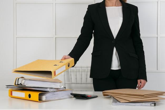 Geschäftsdokumentenkonzept: mitarbeiterfrauenhände, die in stapeldateien für die suche arbeiten