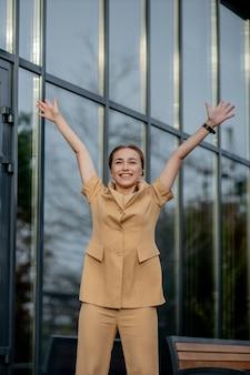 Geschäftserfolg glückliche junge geschäftsfrau, die arbeitskarriereerfolge mit beiden händen gegen bürogebäude feiert.