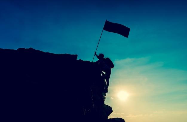 Geschäftserfolg und zielkonzept. silhouette kletterer auf der klippe.