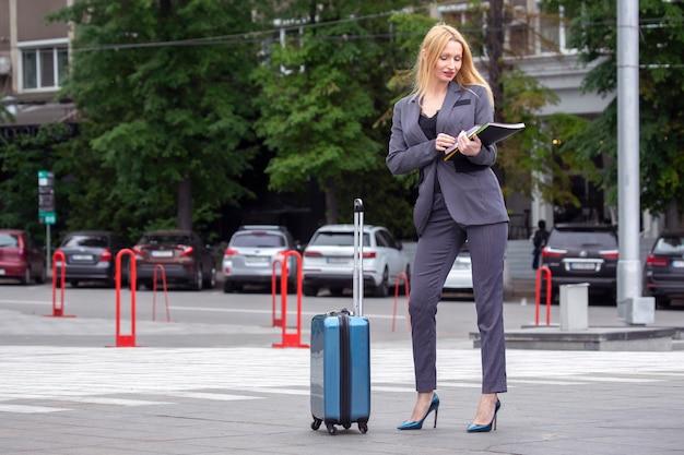Geschäftserfolgreiche frau mit reisekoffer mit dokumenten in der hand auf stadtstraße