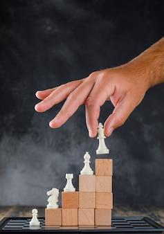 Geschäftserfolgskonzept mit schachbrett-seitenansicht. mann, der figur auf pyramide der blöcke setzt.