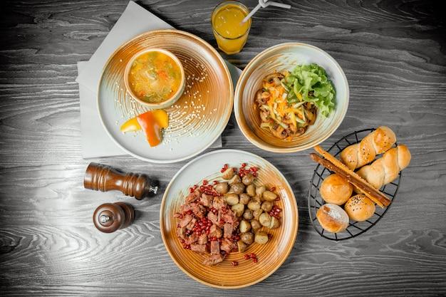 Geschäftsessen gegrilltes rotes fleisch mit bratkartoffeln gemüsesuppe pilzsalat brot getränk und schwarzer pfeffer auf dem tisch