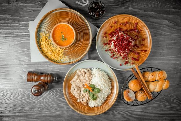 Geschäftsessen tomado-suppe mit käse granatapfelsalat huhn stroganoff mit reisbrot getränk und schwarzem pfeffer auf dem tisch