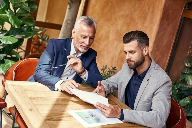 Geschäftsessen zwei geschäftsleute im restaurant sitzen am tisch und diskutieren über das projektfreudige team