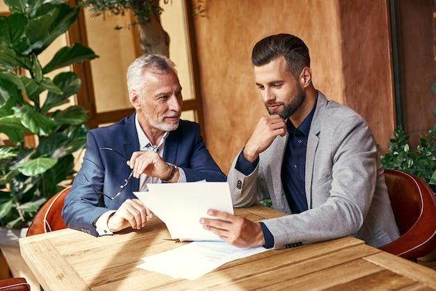 Geschäftsessen zwei geschäftsleute im restaurant sitzen am tisch und diskutieren über den vertrag lächelnd