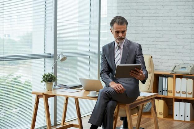 Geschäftsfachmann, der mit digitaler tablette in seinem umweltfreundlichen büro gesetzt auf dem hölzernen schreibtisch arbeitet