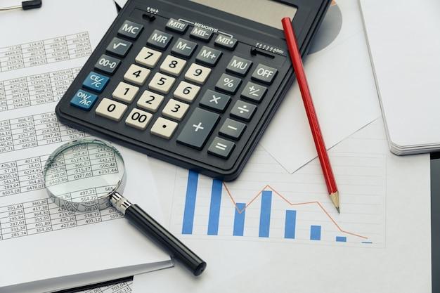 Geschäftsfinanzdokumente, bürorechner und stift auf dem tisch. zahlen und grafiken