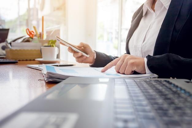 Geschäftsfrau am arbeiten mit finanzberichten und laptop-computer im büro