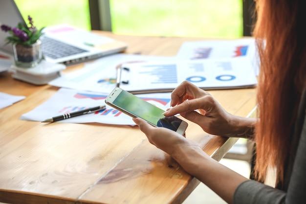 Geschäftsfrau am arbeiten mit finanzberichten und verwenden des beweglichen smartphone im büro