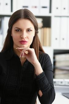 Geschäftsfrau am arbeitsplatz im büroporträt in einem einfachen anzug lächelt und schaut schafft einen auftritt von arbeit und erfolg schafft vertrauen.