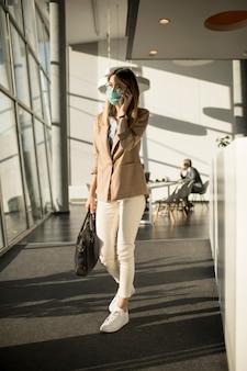 Geschäftsfrau am handy, die im büro geht und maske als virenschutz trägt
