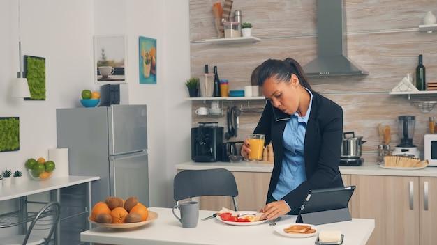 Geschäftsfrau am telefon beim frühstücken. konzentrierte geschäftsfrau morgens multitasking in der küche bevor es ins büro geht, stressige lebensweise, karriere und ziele zu erreichen