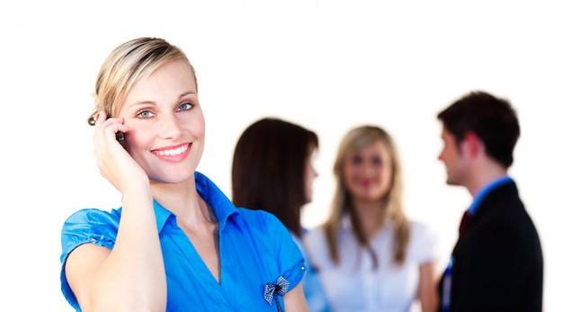 Geschäftsfrau am telefon mit ihrem team im hintergrund
