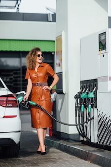 Geschäftsfrau an der tankstelle, während sie ihr auto befüllt