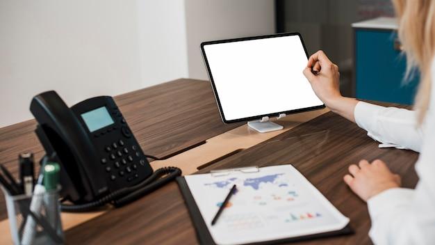 Geschäftsfrau an ihrem büro unter verwendung einer tablette