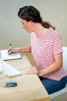 Geschäftsfrau an ihrem schreibtisch in ihrem planer schreiben