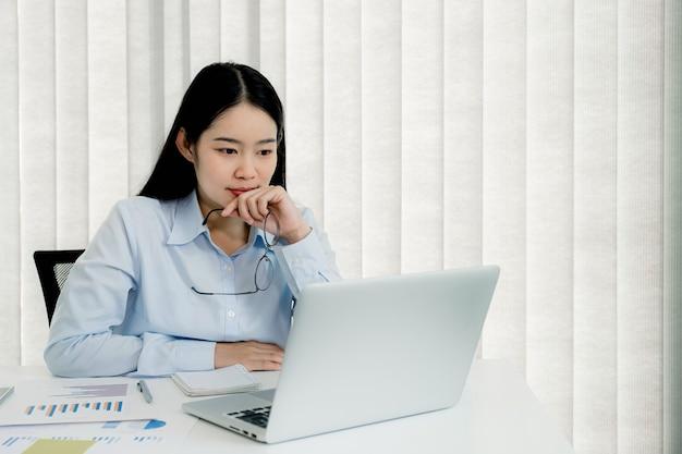 Geschäftsfrau analysiert das diagramm und trifft videokonferenzen mit laptop im homeoffice