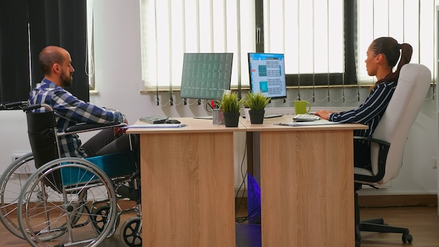 Geschäftsfrau analysiert finanzstatistiken im gespräch mit behinderten mitarbeitern, die im rollstuhl sitzen und grafiken auf dem schreibtisch im bauamt überprüfen. behinderter geschäftsmann mit moderner technologie