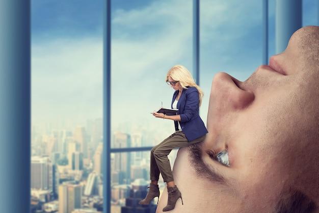 Geschäftsfrau-analystin sitzt auf dem männlichen gesicht