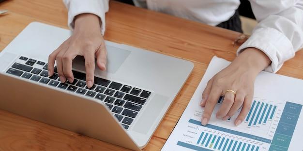 Geschäftsfrau anlageberater, der die bilanz des jahresfinanzberichts des unternehmens analysiert, der mit dokumentendiagrammen arbeitet. konzeptbild von geschäft, markt, büro, steuer.