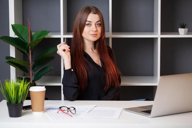 Geschäftsfrau arbeitet im büro an einem weißen tisch