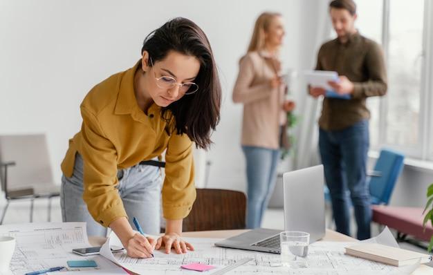 Geschäftsfrau arbeitet, während ihre teamkollegen sprechen