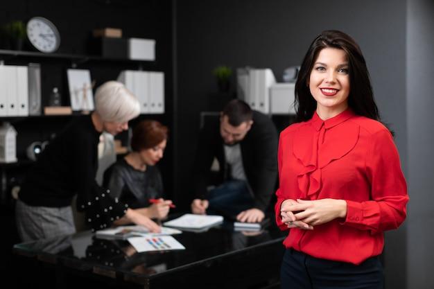 Geschäftsfrau auf dem hintergrund von den büroangestellten, die projekt besprechen