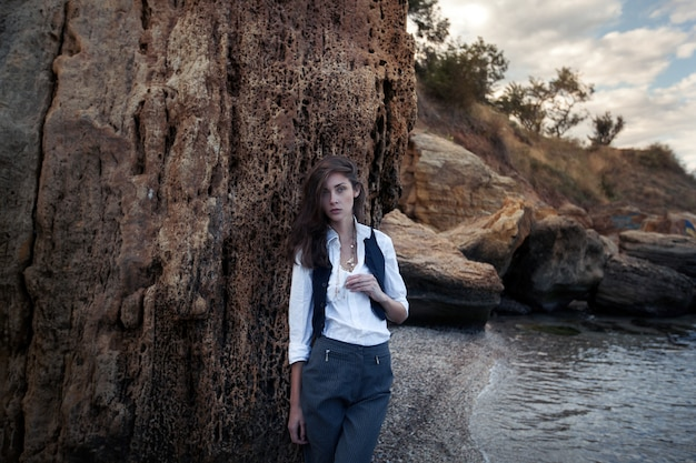 Geschäftsfrau auf der anzugsweste und weißem hemd, die nahe großem stein auf dem meer stehen, kostete