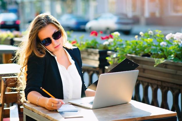 Geschäftsfrau auf der straße im computer an einem tisch in einem café