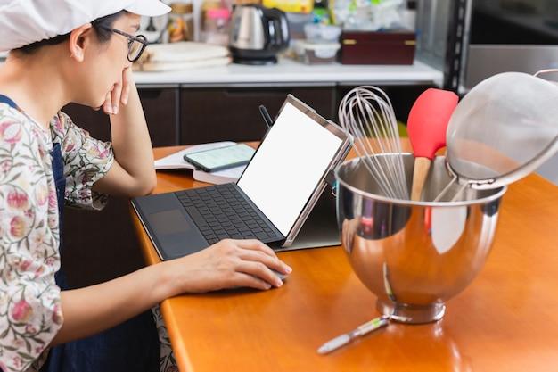 Geschäftsfrau bäcker arbeitet am laptop mit bäckereiausrüstung auf dem tisch