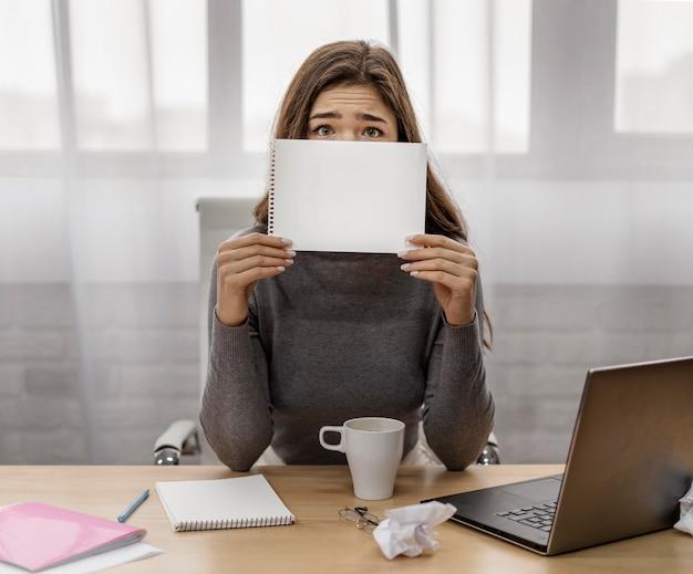 Geschäftsfrau bedeckt ihr gesicht mit einem leeren notizblock