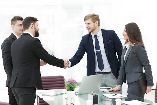 Geschäftsfrau begrüßt den angestellten mit einem handschlag