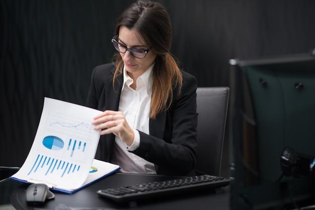 Geschäftsfrau bei der arbeit in ihrem firmenbüro, das papierkram liest