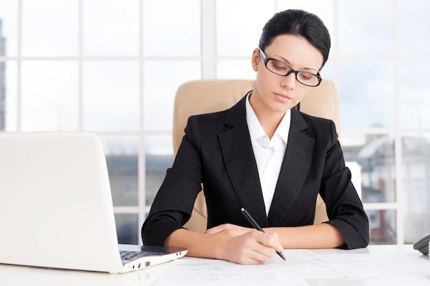Geschäftsfrau bei der arbeit. selbstbewusstes junges unternehmen, das etwas auf papier schreibt, während sie an ihrem arbeitsplatz sitzt