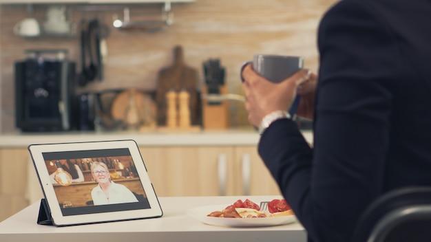 Geschäftsfrau bei einem videoanruf mit ihrer mutter während des frühstücks. mit moderner online-internet-webtechnologie per webcam-videokonferenz-app mit verwandten, familie, freunden und kollegen chatten