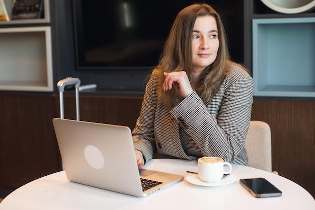 Geschäftsfrau benutzt das telefon, um nachrichten und finanzdiagramme zu überprüfen
