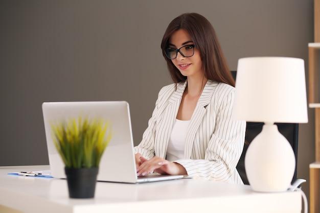 Geschäftsfrau benutzt einen laptop und lächelt, während sie im büro arbeitet.
