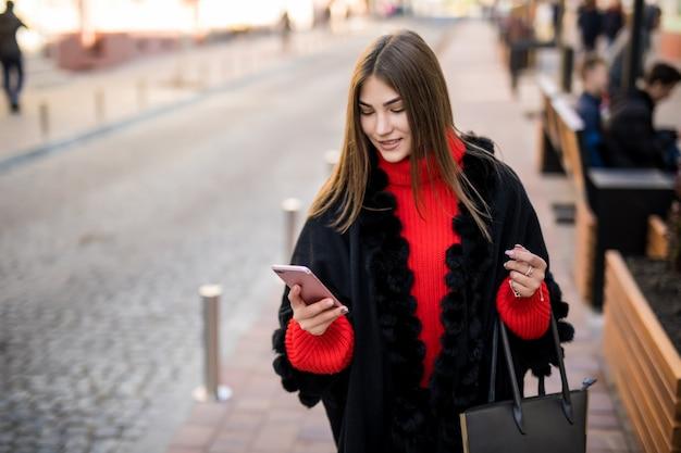 Geschäftsfrau benutzt smartphone auf der straße beim gehen