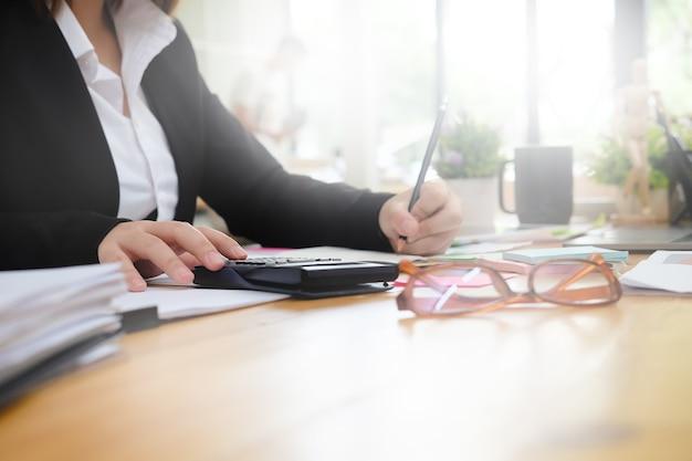 Geschäftsfrau berechnen finanzdaten über arbeitsplatz mit morgenlicht.
