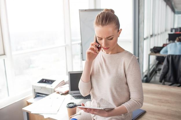 Geschäftsfrau betrachtet die tablette und spricht gleichzeitig am telefon